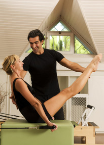 Photo of a fitness professional specializing in Pilates training a female client.