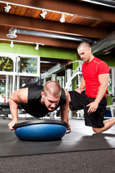 Photo of a male fitness trainer working on a male client.